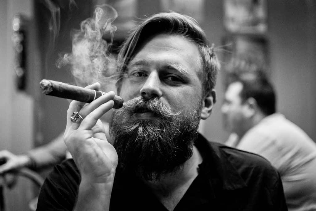 man smoking cigar in bar