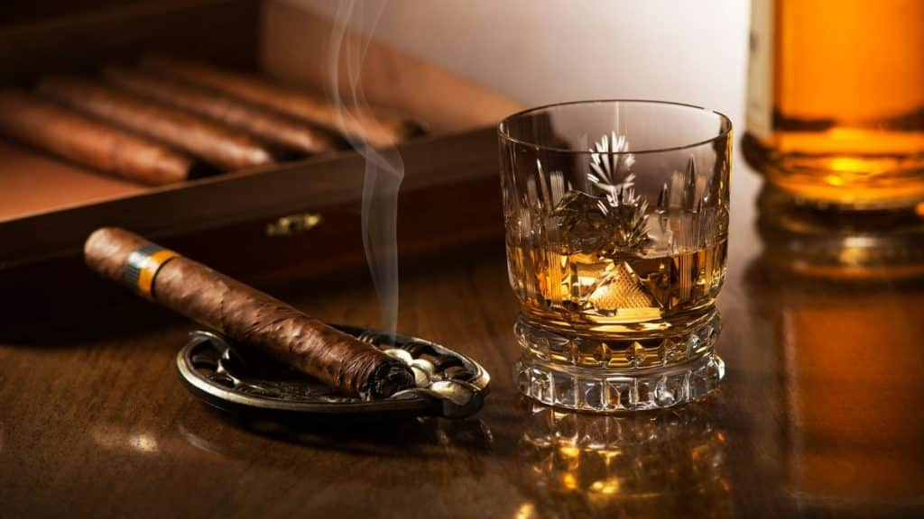 cigar by scotch on bar